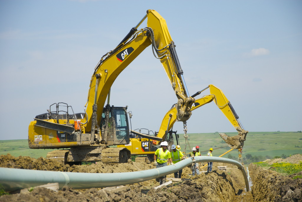 Welded pipeline being lowered into the trench using backhoes. Image courtesy: Alliance Pipeline.